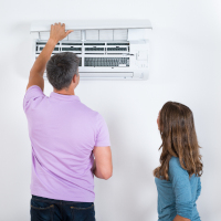 Couple checking air conditioner